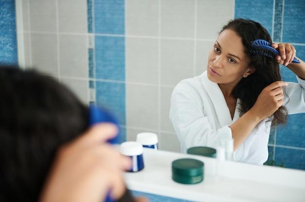 흰색 와플 목욕 가운을 입은 매력적인 히스패닉 여성이 욕실에서 머리를 빗으면서 거울 반사를 바라보고 있습니다.