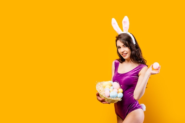 Привлекательная горячая молодая женщина, носящая боди и уши кролика, держа корзину с цветными пасхальными яйцами, позируя на желтой стене.