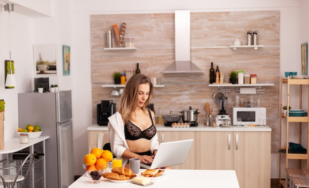 Attractive housewife wearing sexy lingerie typing on laptop during breakfast. attractive blonde lady with tattoos using pc sitting in the kitchen dressed in seductive underwear smiling.