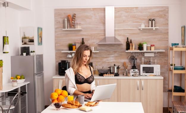 朝食時にラップトップでタイピングセクシーなランジェリーを着ている魅力的な主婦。魅惑的な下着の笑顔に身を包んだキッチンに座っているpcを使用して入れ墨を持つ魅力的なブロンドの女性。