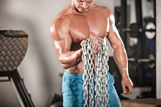Attractive hunky black male bodybuilder in gym with iron chains