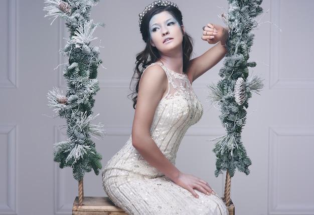 ブランコに座っている魅力的な氷の乙女