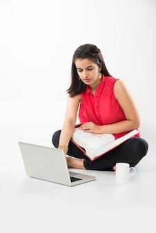 白い床の上に孤立して座って、本の山とラップトップコンピューターで勉強している魅力的なインドのアジアの女の子の学生