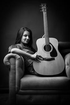 집에서 소파나 소파에 앉아 기타를 연주하거나 들고 있는 매력적인 인도 아시아 소녀