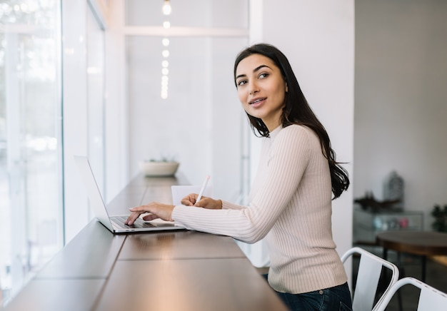 Привлекательная индийская женщина, используя ноутбук, написание заметок, набрав на клавиатуре, работая дома