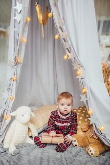 灰色の壁におもちゃで遊ぶ魅力的な幼児の女の子。彼女は白い雄羊とテディベアが大好きです。