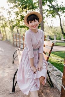 Привлекательная вдохновленная брюнетка в длинном старомодном платье позирует возле деревянной скамейки и улыбается