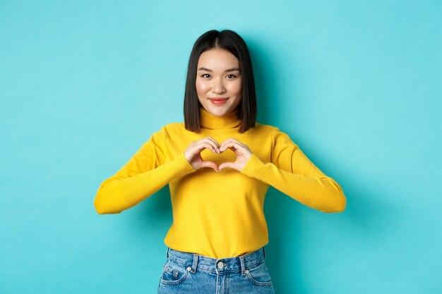 黄色いセーターを着た魅力的な日本人の女の子、ハートのジェスチャーを見せて、私はあなたを愛していると言い、カメラを心から見て、青い背景の上に立っています。