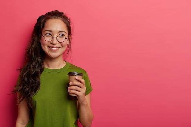 Attraente donna asiatica gioiosa con lunga coda di cavallo, beve caffè da asporto prima della giornata lavorativa, ricorda qualcosa di piacevole mentre beve bevanda, vestita con abbigliamento casual, occhiali rotondi sembra felice da parte