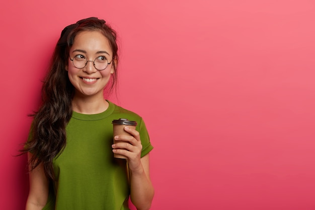 긴 포니 테일이있는 매력적인 즐거운 아시아 여성, 근무일 전에 테이크 아웃 커피를 마시고, 음료를 마시면서 즐거운 것을 기억하고, 캐주얼 한 옷을 입고, 둥근 안경은 옆으로 기뻐 보입니다.