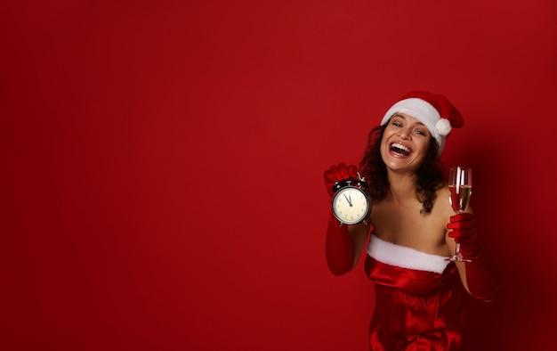 サンタカーニバルの衣装を着た魅力的な楽しいブルネットの女性は、美しい歯を見せる笑顔で笑い、スパークリングワインと目覚まし時計を持って真夜中をダイヤルします。クリスマス広告用のコピースペース