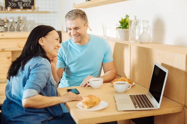 Attractive joyful dark-haired woman and a handsome alert blond man sitting at the table in a cafe and listening to music and having coffee