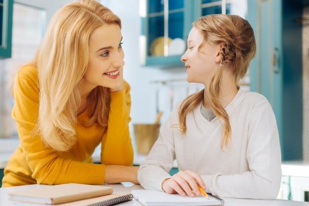 Привлекательная радостная светловолосая девушка улыбается и держит карандаш, пока она и ее мать смотрят друг на друга
