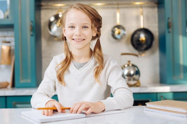 Привлекательная радостная светловолосая девушка улыбается и держит карандаш, сидя за столом со своими блокнотами