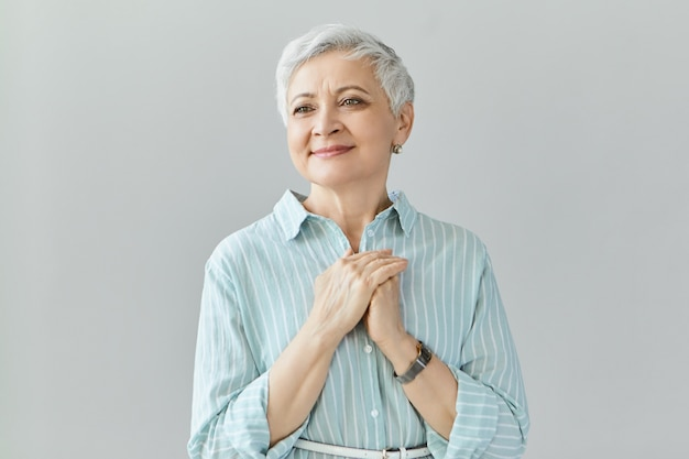 Attractive joyful female in her sixties posing isolated being touched by heart piercing story or movie, looking with pleased happy smile, holding hands clasped on chest. kindness and gratefulness