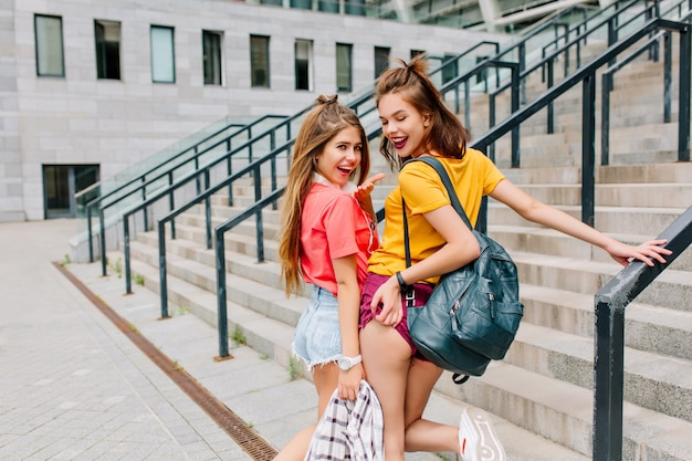 Attractive joyful girls spending time together and posing on the steps, looking over shoulder with smile