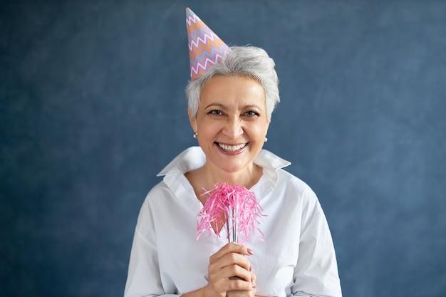 Attraente donna matura allegra con capelli grigi in posa isolata con il fischio