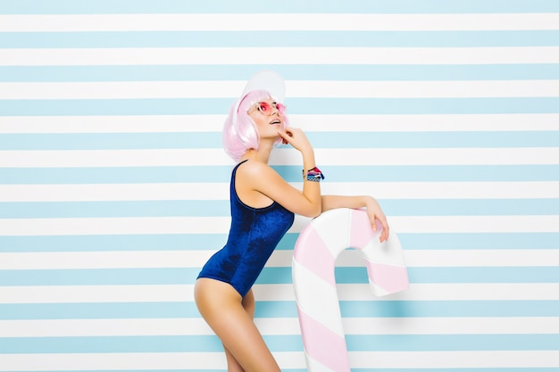 Attractive joyful sexy young model in blue bodysuit, with cut pink hairstyle, in pink sunglasses chilling with big lollipop on striped blue white wall. beach summer time, smiling, leisure.