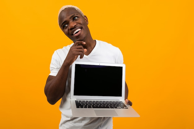 Attractive joyful smiling american man holding laptop with mockup and dreaming on yellow background