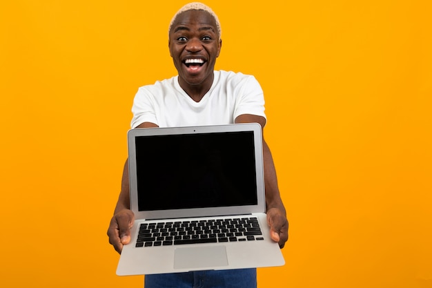 Attractive joyful surprised american man holds out his hands with laptop with mockup on yellow background