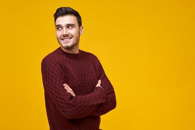Attraente gioioso giovane uomo che indossa pullover lavorato a maglia di buon umore, distoglie lo sguardo con un sorriso felice e fiducioso, tenendo le braccia incrociate sul petto. ragazzo carino in posa del ponticello isolato