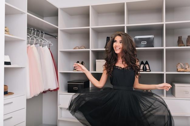 Attraente gioiosa giovane donna con lunghi capelli ricci bruna disegno nel guardaroba di lusso. piacevolmente sorpreso, aspetto elegante, modello alla moda, ricerca, sogno, stile, felicità