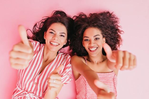 매력적인 여성들은 기쁨으로 불을 밝히고 큰 엄지 손가락을 보여줍니다. 쾌활한 검은 머리 소녀