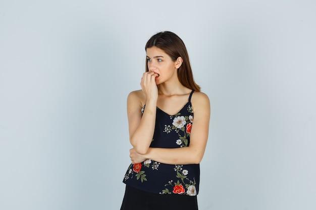 블라우스에 손톱을 물어뜯고 걱정스러운 표정을 짓고 있는 매력적인 여성.