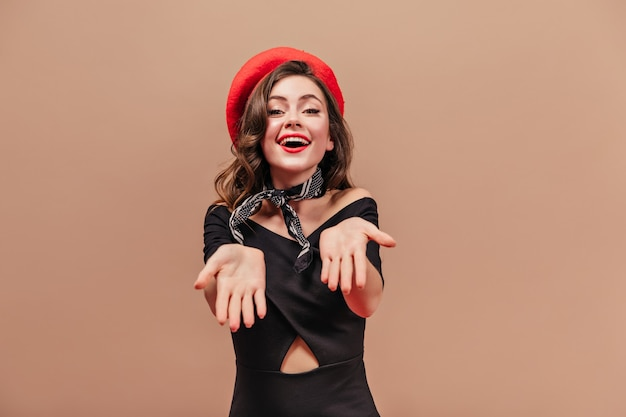 La signora attraente in vestito nero e cappello rosso sta sorridendo e mostrando i suoi palmi.