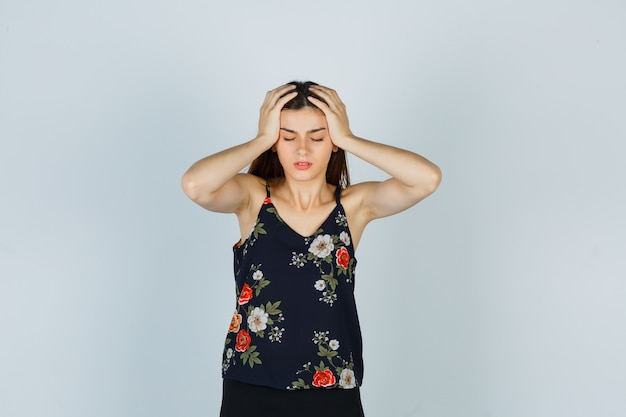 Attraente signora in camicetta che si tiene per mano sulla testa e sembra addolorata, vista frontale.
