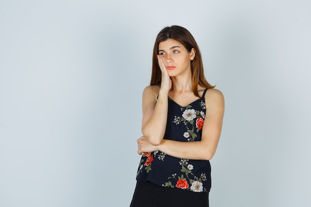 Attractive lady in blouse keeping hand on cheek while looking aside and looking displeased , front view.
