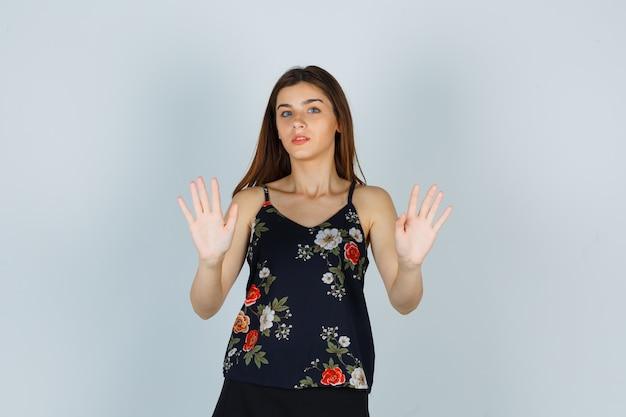 Signora attraente in camicetta che alza le mani per difendersi e sembra terrorizzata, vista frontale.