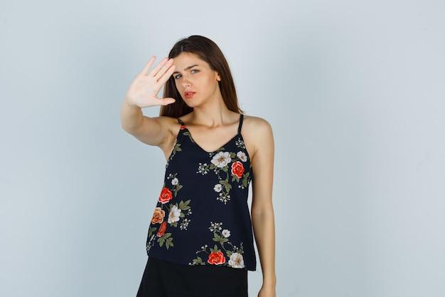 Attraente signora in camicetta che mostra il gesto di arresto e sembra spaventata, vista frontale.