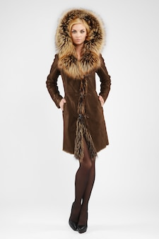 Attractive lady in brown sheepskin coat posing with fur hood on her head