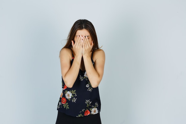 Attractive lady covering face with hands in blouse and looking ashamed , front view.