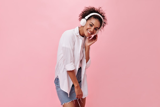 Attractive lady in denim skirt listens to music on pink wall