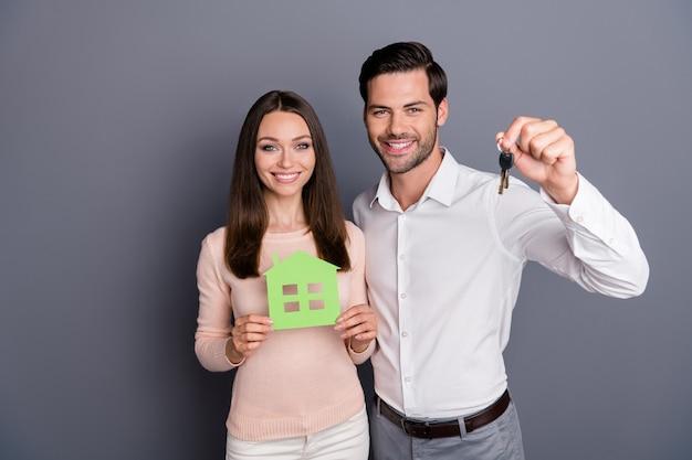 魅力的な女性ハンサムな男は緑の紙の家のキーホルダーを保持します