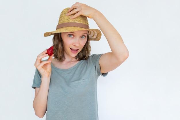 Signora attraente in cappello che tiene fragola e saluto maturi