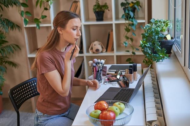 自宅でオンラインメイクアップコース中にリップライナーを保持している魅力的な女性