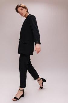 Привлекательная дама в черном наряде позирует на изолированном фоне. портрет молодой женщины в полный рост внутри темного костюма