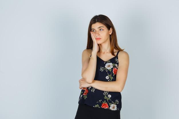 Привлекательная дама в блузке держит руку на щеке, глядя в сторону и недоволен, вид спереди.