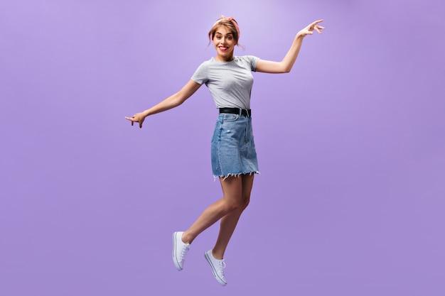Привлекательная дама в джинсовой одежде jump.n фиолетовом фоне. красивая молодая женщина в рубашке и стильной юбке позирует на изолированном фоне.