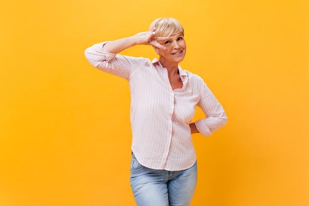 데님 바지와 핑크색 셔츠를 입은 매력적인 아가씨는 평화 기호를 보여줍니다.