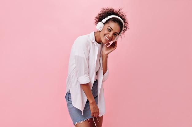 ピンクの壁で音楽を聴くデニムスカートの魅力的な女性