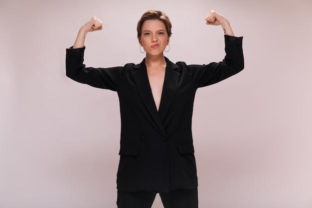Привлекательная дама в костюме, показаны мышцы на белом фоне. мощная короткошерстная женщина в черной куртке демонстрирует бицепс на изолированном