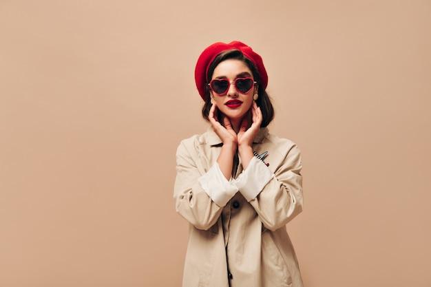 Привлекательная дама в солнечных очках и красном берете позирует на бежевом фоне. замечательная девушка в осеннем легком пальто и яркой шляпе смотрит в камеру.