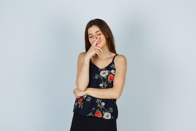 Signora attraente che tiene il dito sulle labbra mentre sorride in camicetta e sembra allegra. vista frontale.