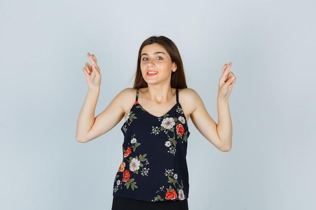 Signora attraente che tiene le dita incrociate in camicetta e sembra ottimista, vista frontale.