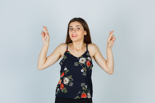 ブラウスで指を交差させ、楽観的な正面図を見て魅力的な女性。