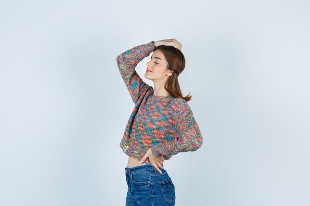 머리에 손을 얹고 스웨터, 청바지를 입고 눈을 감고 평화롭게 보이는 매력적인 여성. .